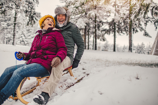 Photo of a lovely, elderly couple who still enjoy sledding as when they were kids