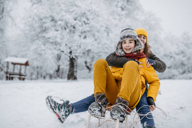 Sledding time Friends having fun on sled in winter, they are sledding in the snow. 12 17 months stock pictures, royalty-free photos & images