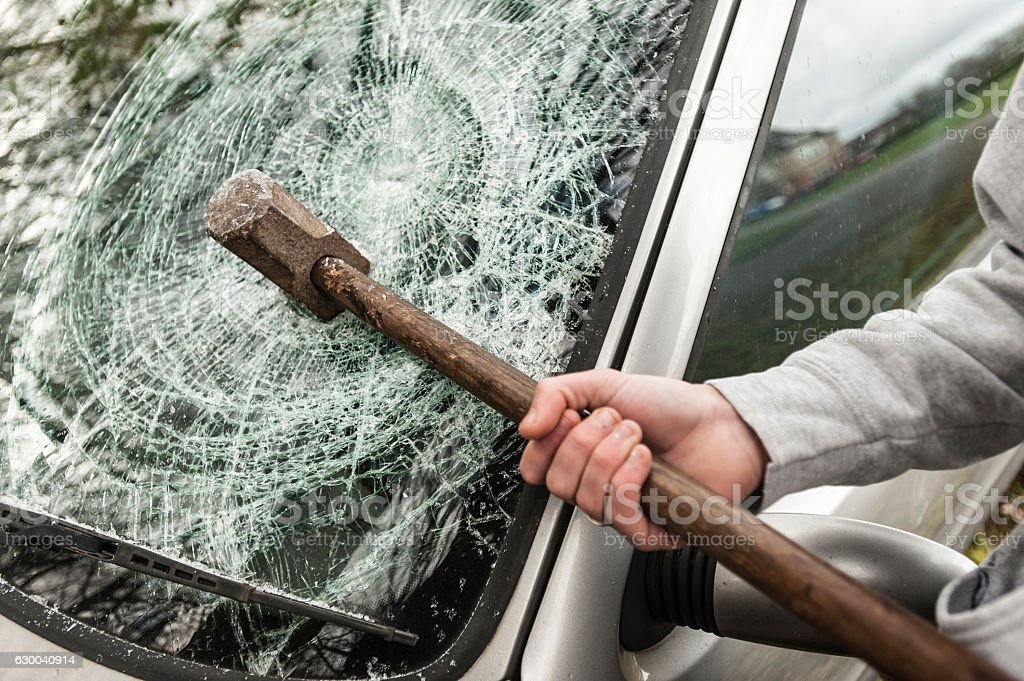 Sledge Hammer in a car windscreen. stock photo