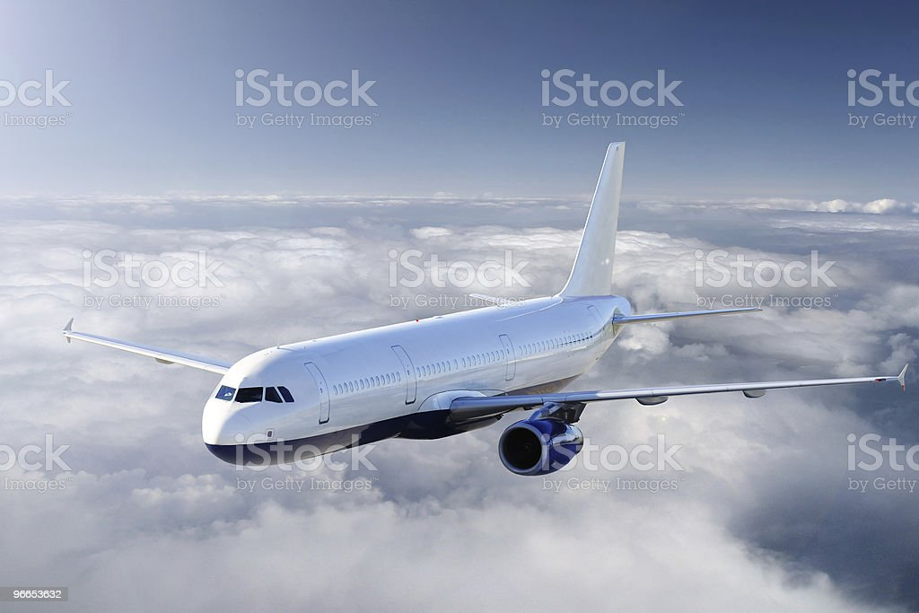 A sleek jetliner soars above the clouds royalty-free stock photo