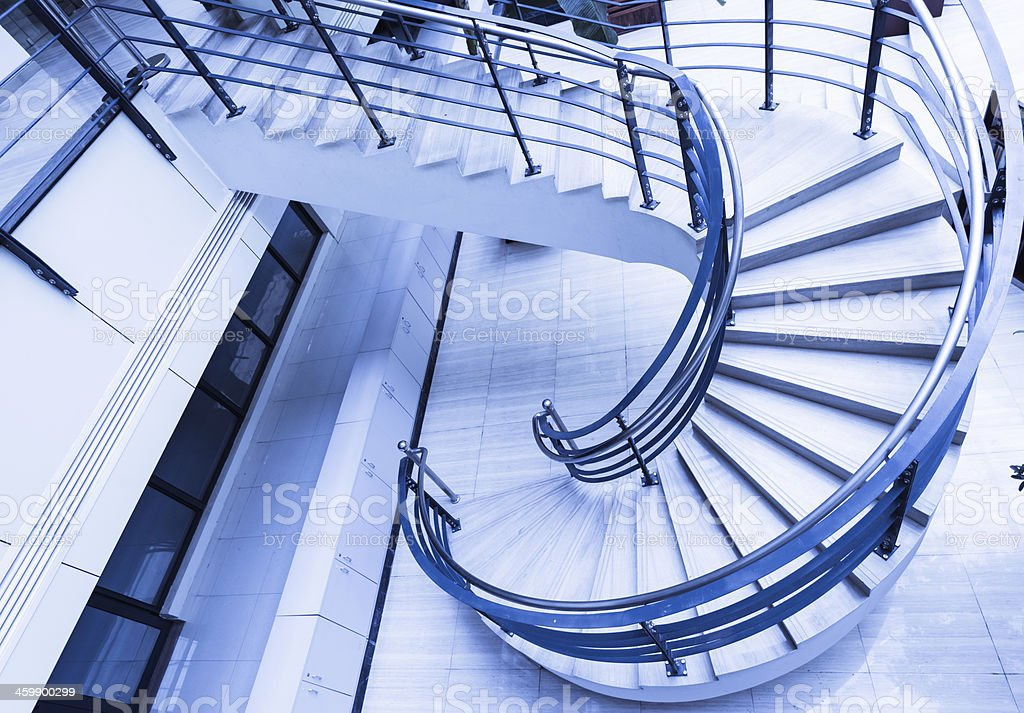Sleek metal spiral staircase, modern architectural interior decoration. royalty-free stock photo