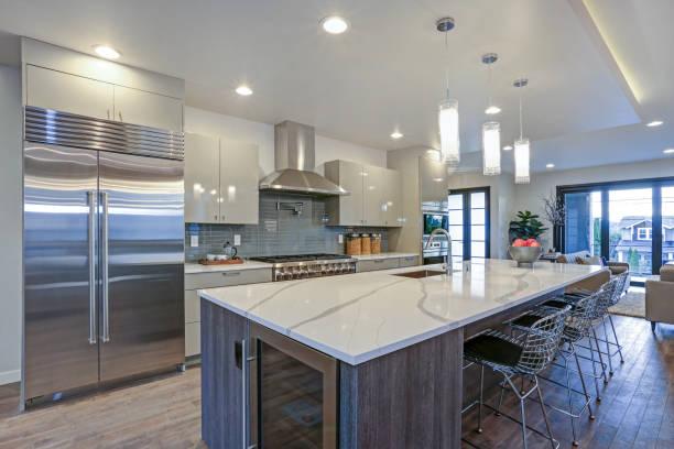 Sleek modern kitchen design with a gray center island stock photo