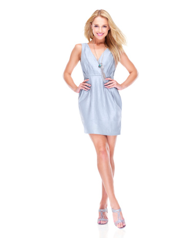 Attractive young woman smiling in a cocktail dress while isolated on white