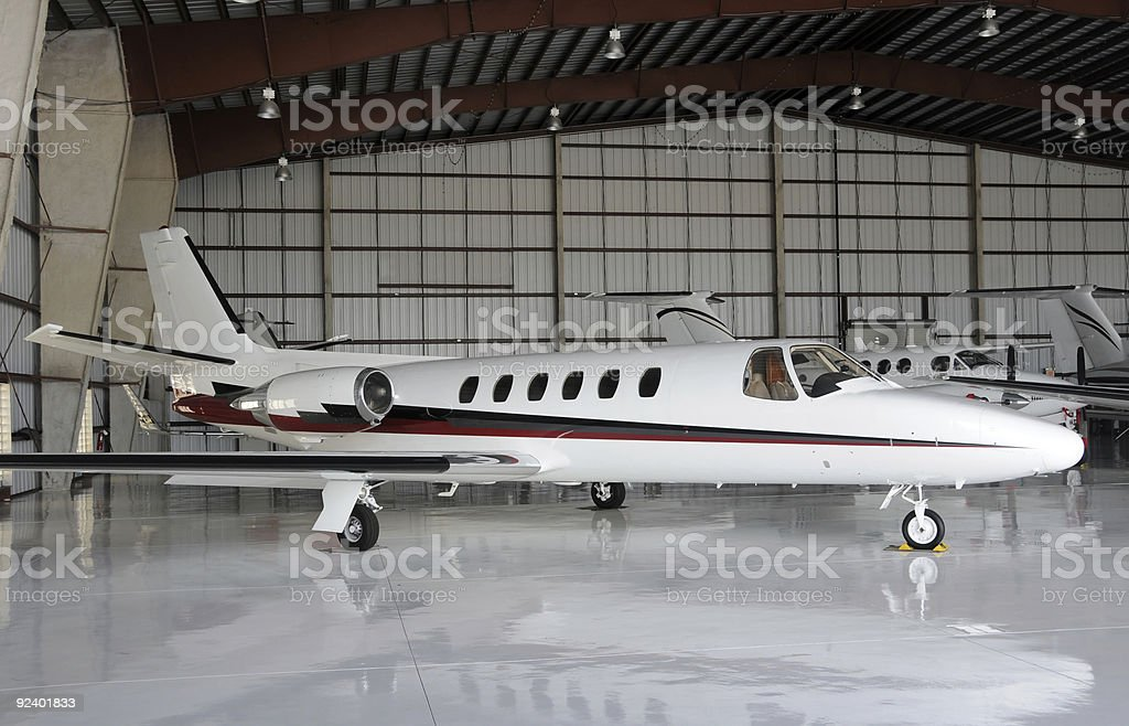 Sleek white private jet, positioned in a hangar stock photo