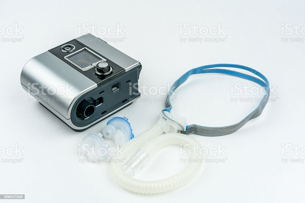 Sleep apnea treatment. CPAP machine with hose and mask. stock photo