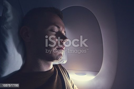 Traveling by airplane. Young passenger sleeping during flight.