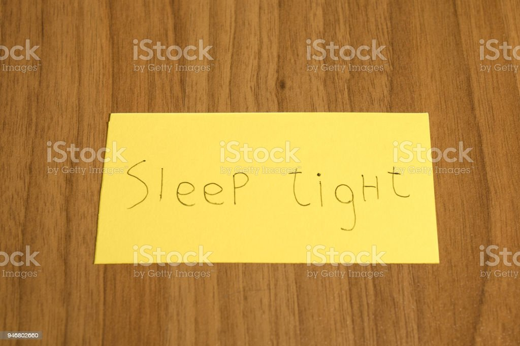 Sleep tight handwrite on a yellow paper with a pen on a table composition stock photo