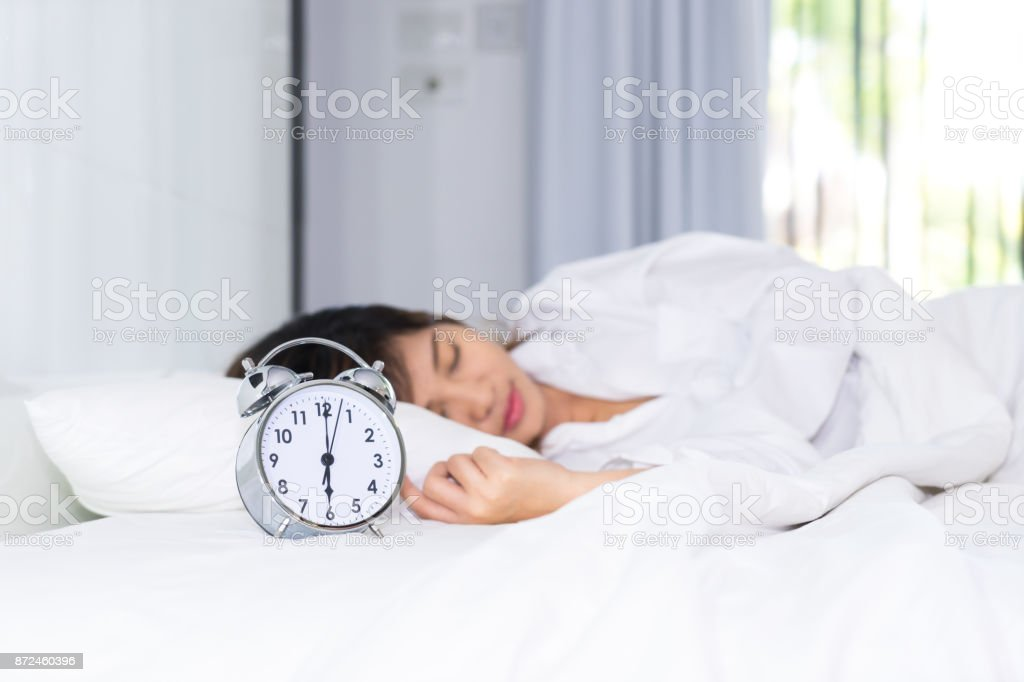 Sleep woman in the morning with alarm clock
