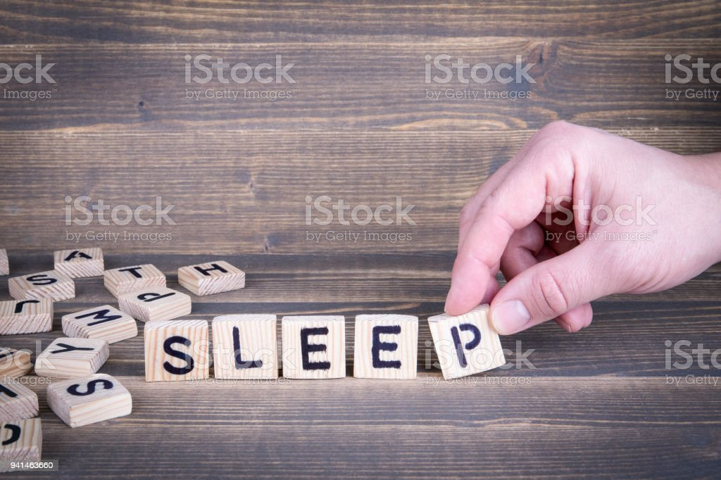 Dormi. Letras de madeira sobre a mesa de escritório - foto de acervo