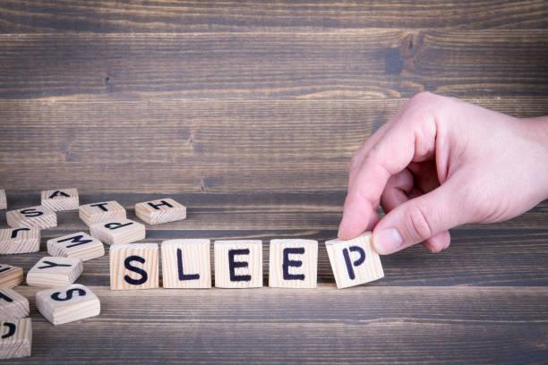 schlafen. holzbuchstaben auf den schreibtisch - gute nacht text stock-fotos und bilder