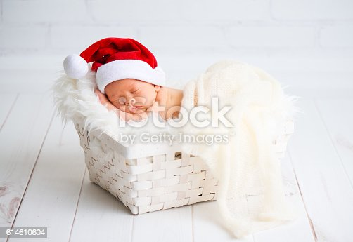 istock sleeper newborn baby in  Christmas Santa cap 614610604