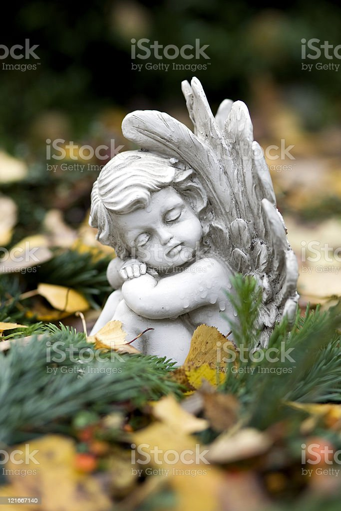 Sleeping angel sitting on a grave stock photo