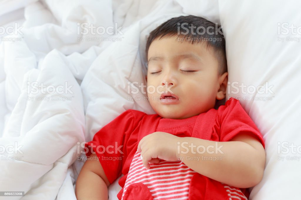 Sleeping Asian baby in his bed and sweet dream stock photo