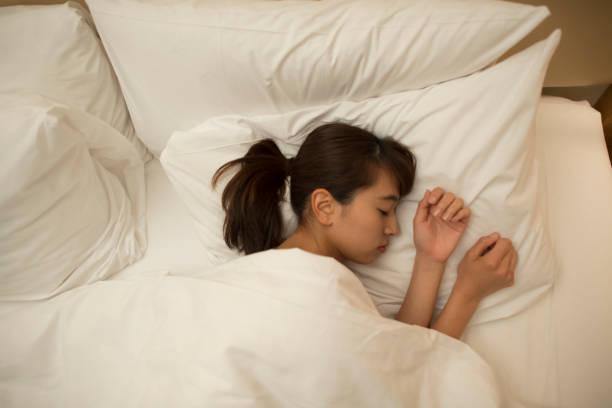 asiatische frauen schlafen - verwandlungskissen stock-fotos und bilder