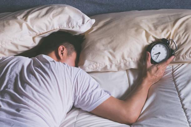 Asya genç erkek rahatsız çalar saat tarafından sabah yatakta uyuyor. stok fotoğrafı