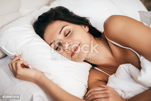 Beautiful young woman smiling during sleeping while lying in the bed at home