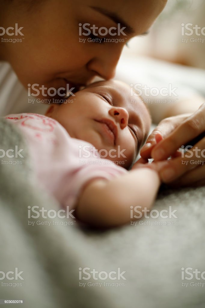 Sleeping baby and mother at home stock photo