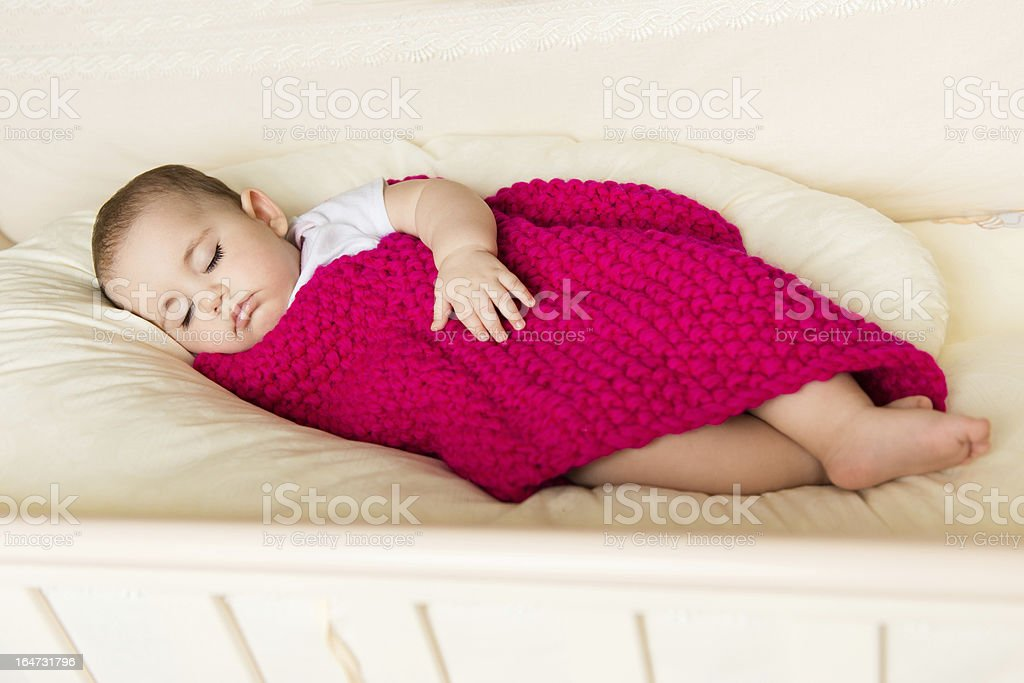 Sleeping baby covered with knitted blanket royalty-free stock photo