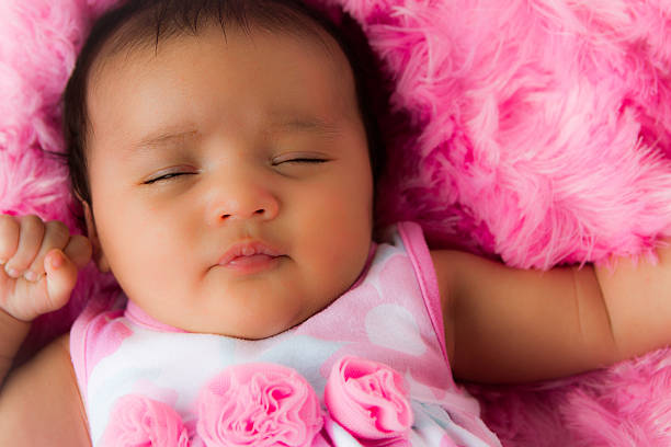Sleeping Baby Girl in Pink Baby girl sleeping on a soft, fuzzy pink blanket. neicebird stock pictures, royalty-free photos & images