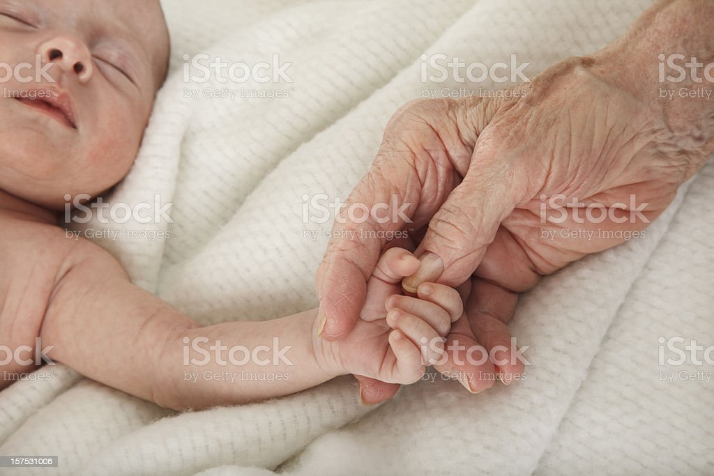 sleeping baby holding great grandmother's hand stock photo