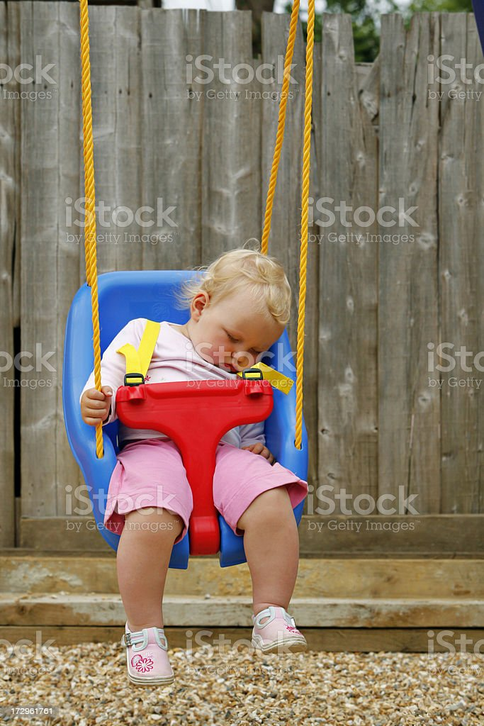 Sleeping baby in a swing stock photo