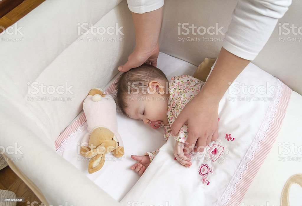 Sleeping baby in crib being held by mother's hands stock photo