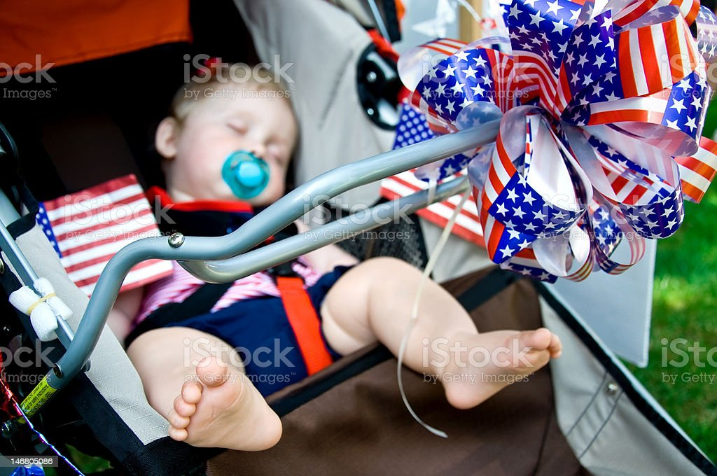 Sleeping baby in stroller on Fourth of July stock photo