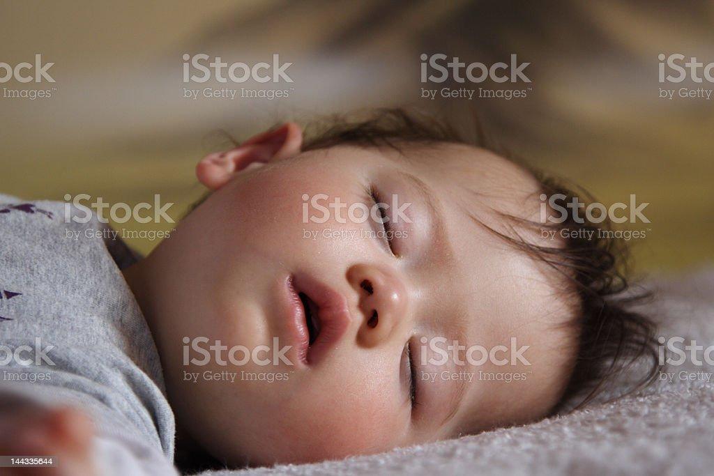 Sleeping baby lying on a gray blanket royalty free stockfoto
