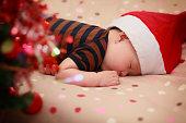 サンタの帽子をかぶって眠っている赤ちゃん