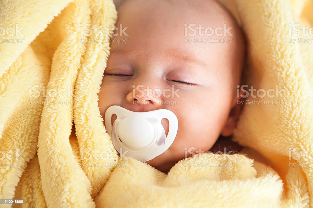 Sleeping Baby With Pacifier In A Yellow Blanket stock photo