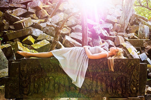 Sleeping Beauty Fairytale Princess Laying on Rock Bed stock photo