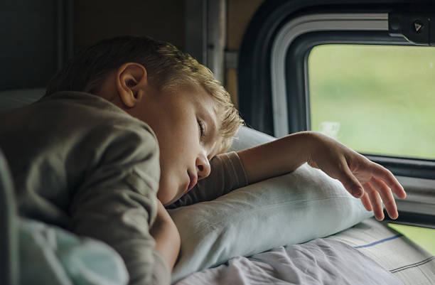 Sleeping boy in front of window stock photo