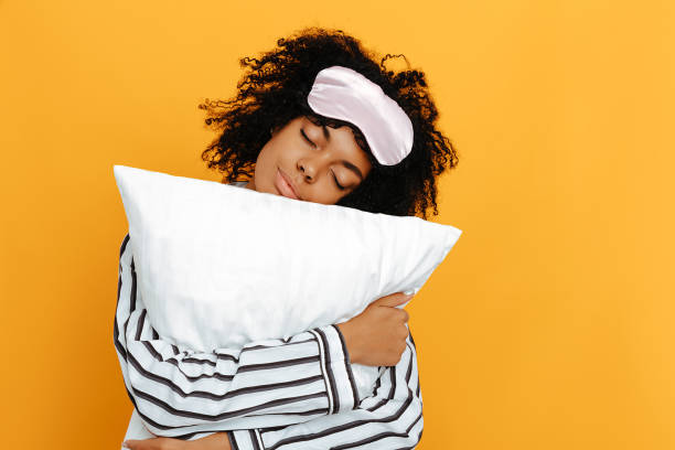 Sleeping. Dreams. Woman portrait. Afro American girl in pajama is hugging a pillow, on a yellow background Sleeping. Dreams. Woman portrait. Afro American girl in pajama is hugging a pillow, on a yellow background sleeping stock pictures, royalty-free photos & images
