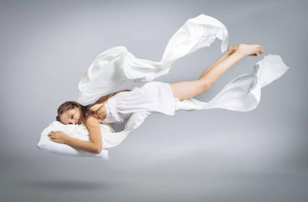 schlafendes mädchen. flug in einem traum. weißes leinen fliegt durch die luft. - traumhaft stock-fotos und bilder