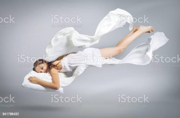 Photo of Sleeping girl. Flight in a dream. White linen flies through the air.