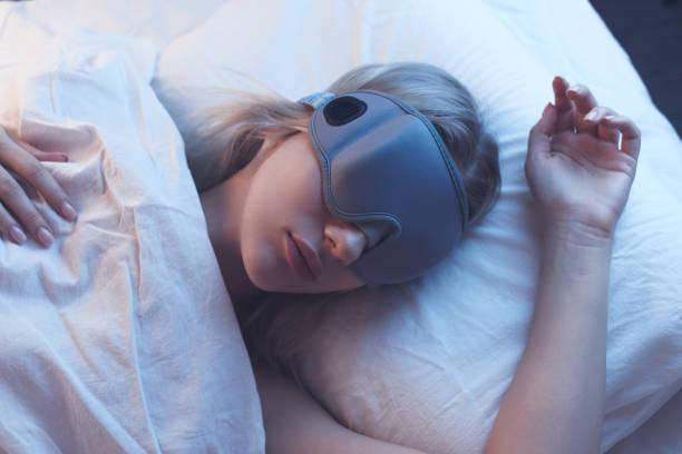 Schlafendes Mädchen in einer Schlafmaske auf einem orthopädischen Kissen mit Nachtbeleuchtung, weiße Bettwäsche. – Foto