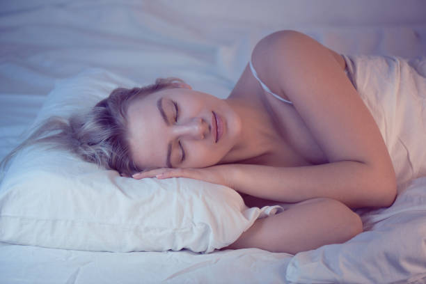 sleeping girl on an orthopedic pillow with night lighting, white linens