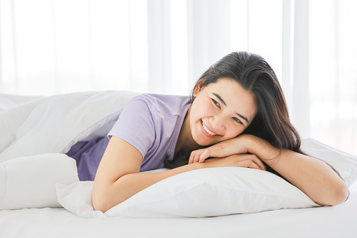 Sleeping girl smiling while lying down on the white bed on her comfy pillow in the morning with copy space