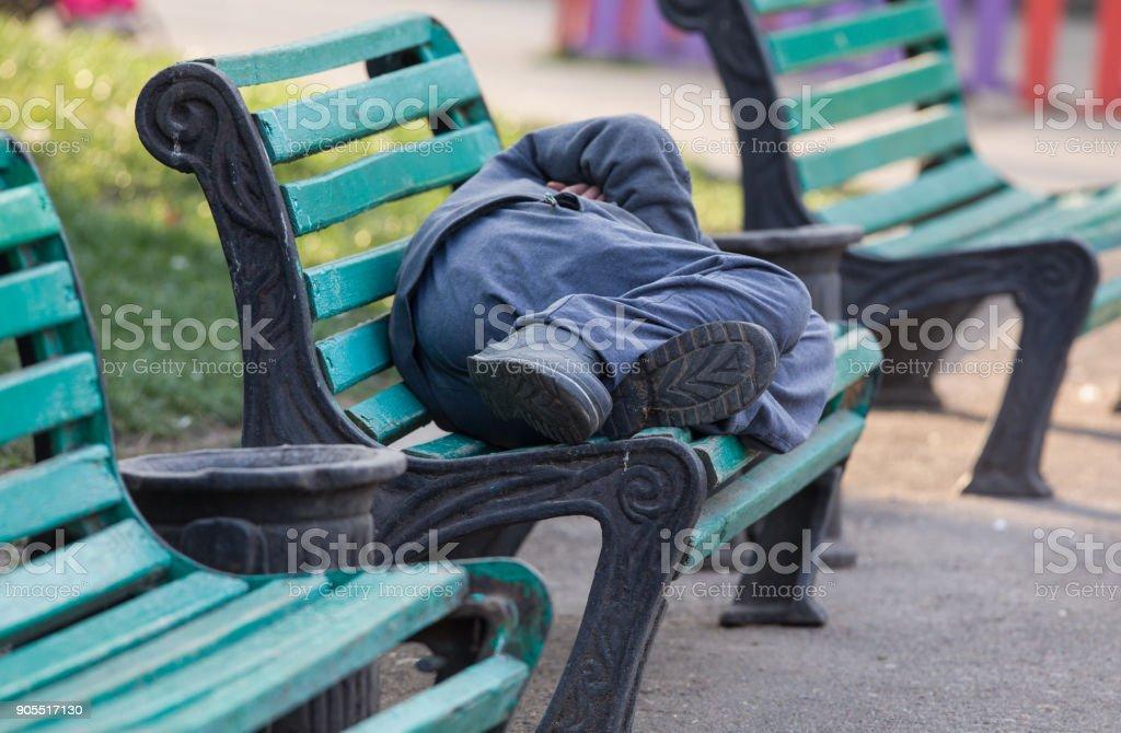 sleeping homeless man on a bench stock photo