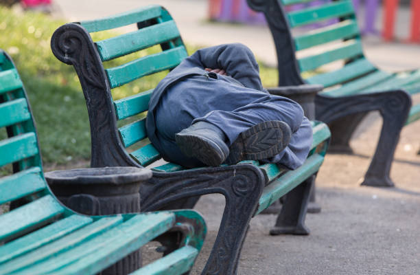 sleeping homeless man on a bench - homelessness stock photos and pictures