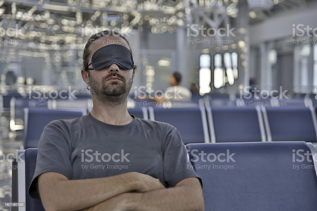 sleeping in airport with eye cover stock photo