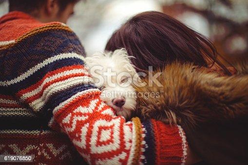 Young couple hugging with their sleepy dog