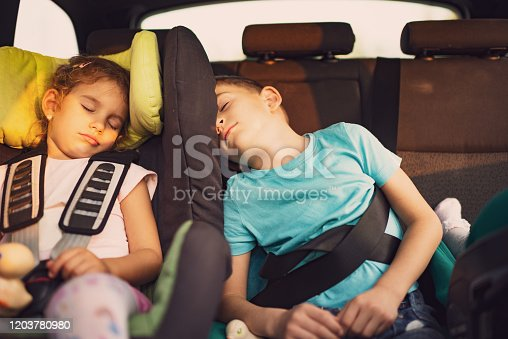 639770050 istock photo Sleeping kids traveling by car 1203780980