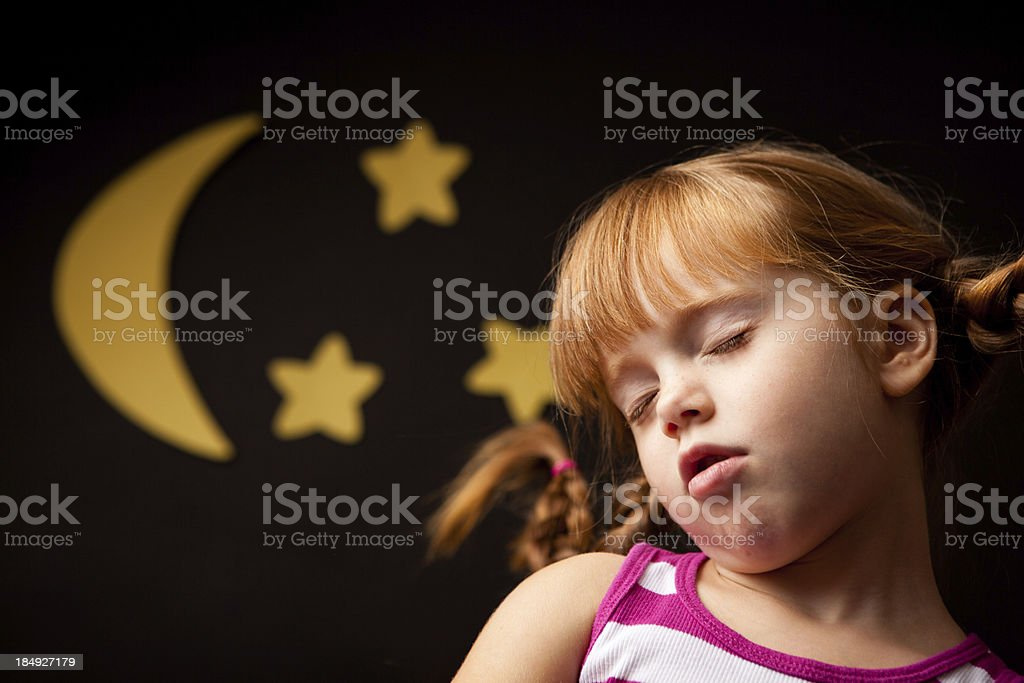 Sleeping Little Girl with Upward Braids By Moon and Stars stock photo