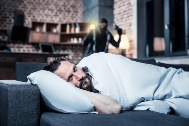 Homem adormecido e um criminoso atrás dele - foto de acervo