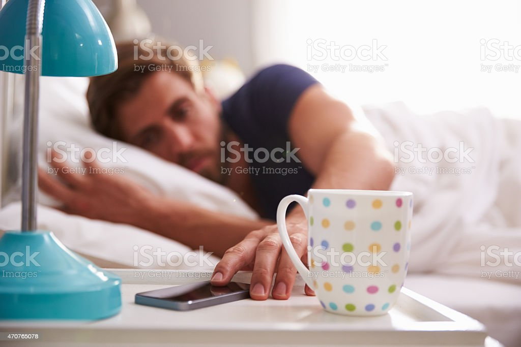 Sleeping Man Being Woken By Mobile Phone In Bedroom stock photo