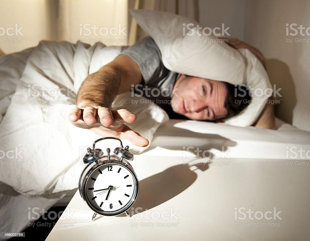 sleeping man disturbed by alarm clock early morning royalty-free stock photo