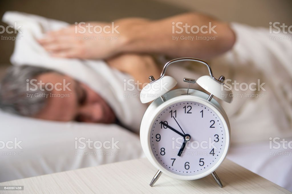 sleeping man disturbed by alarm clock early morning. stock photo