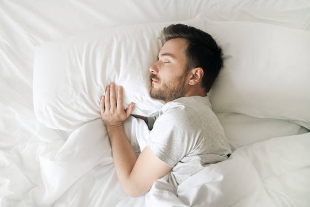 Sleeping man in white bed top view. Relaxed young bearded adult in cozy white bedroom having rest Lifestyle portrait of sleeping man sleeping stock pictures, royalty-free photos & images