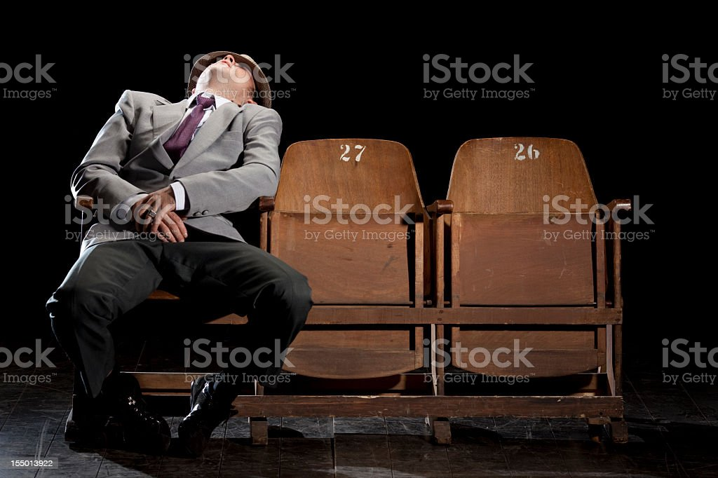 A sleeping man inside a theater house stock photo